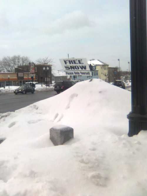 "Sign advertising ""Free Snow"" atop a snow pile"