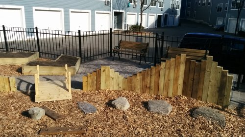 variable height timber wall, stepping stones, and seating area